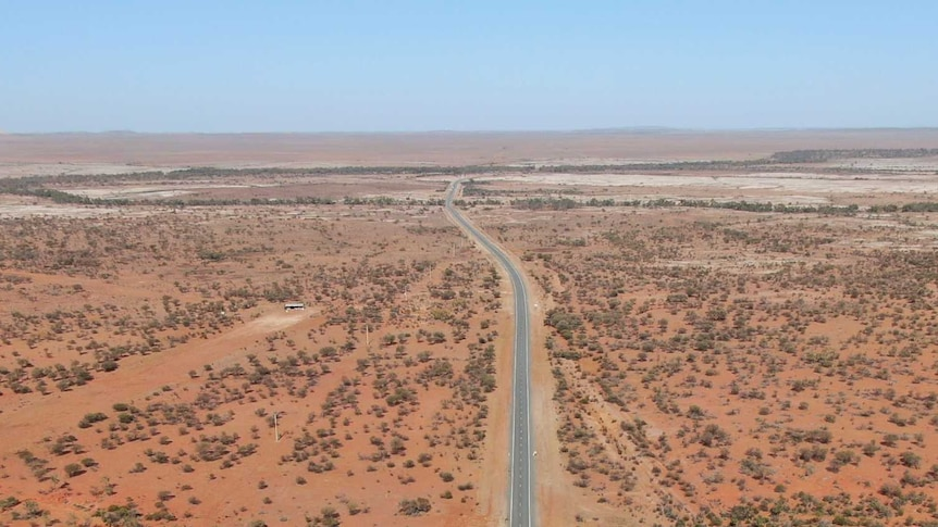 A drone shot of a long stretch of sealed road in the Australian desert.