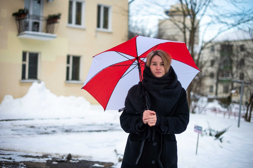 Maria holds a red and white umbrella.