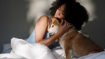 Photo of a woman with curly hair and a light blue singlet hugging a small orange and white dog