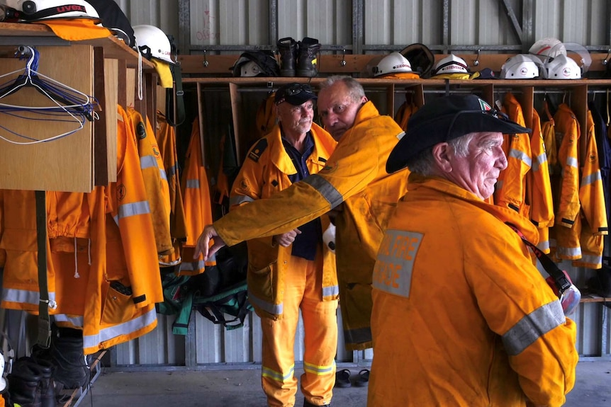Three men wearing firefighting gear stand in a shed surrounded by more equipment.