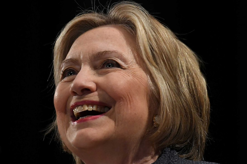 Hillary Clinton smiling in front of a black background
