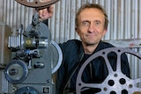 A man poses with a film projector