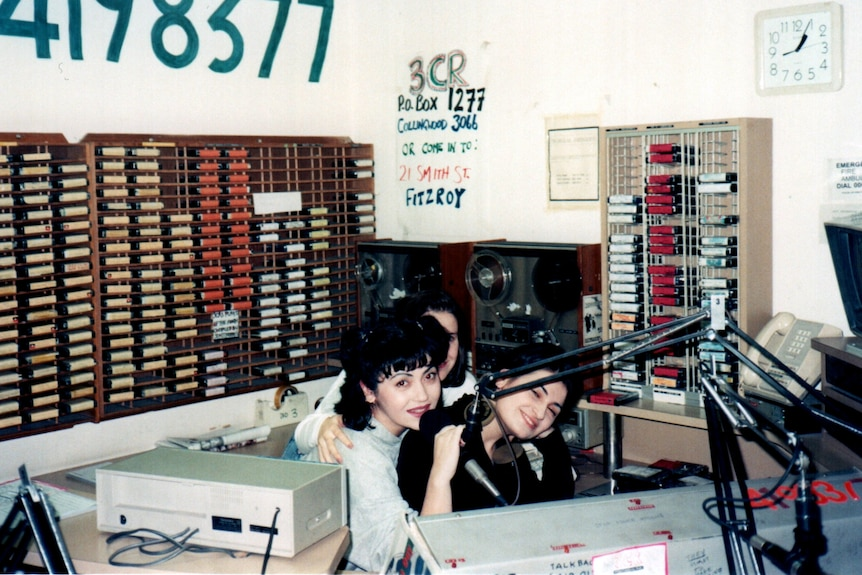 Three young women sit close together in a radio studio