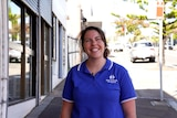 A woman in a blue polo shirt labelled 'Meals on Wheels Port Kembla' grins as she stands on the sidewalk of a street.