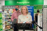 Dr Jeannette Young stands at the microphone while a masked Miles stand behind her in front of prescriptions counter