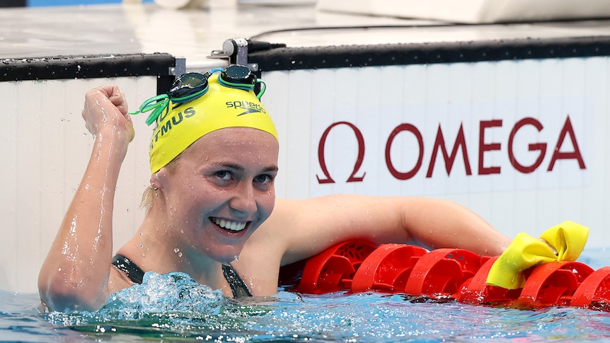 A woman wearing a yellow cap in a pool