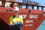 Man in long sleeved shirt and hard hat standing in front of a ship.