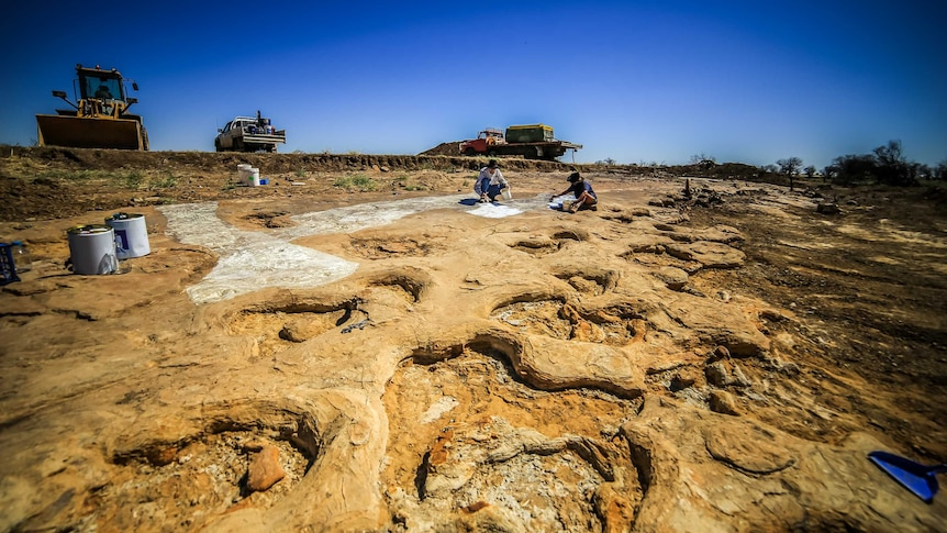 Wide divots in sandstone in the foreground, with people crouching in the dirt and bulldozers in the background under a blue sky.
