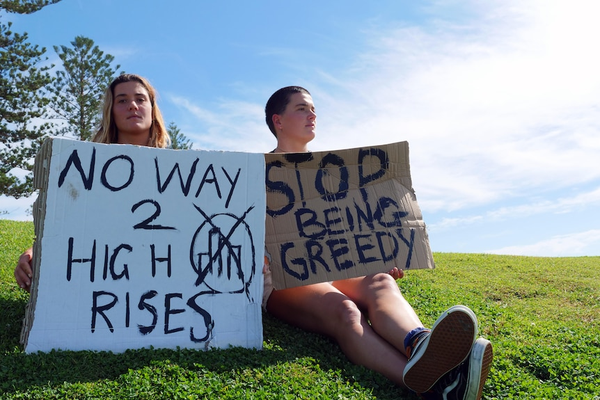 two women sitting with protest placards