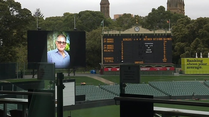 A man's picture on a big screen and words on an old scoreboard at a stadium