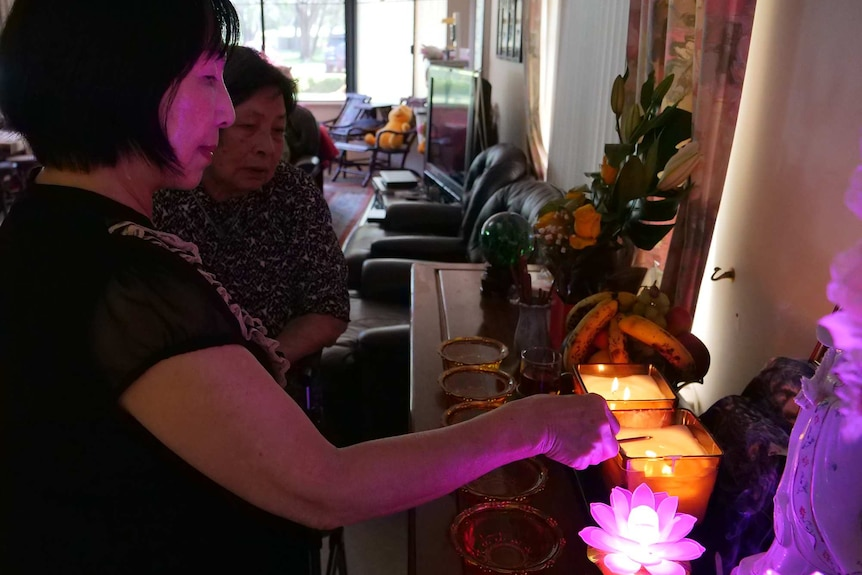 Two women light candles in front of a shrine.