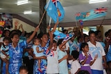 Villagers clap, cheer and wave flags as they look away from the camera to the match on television.