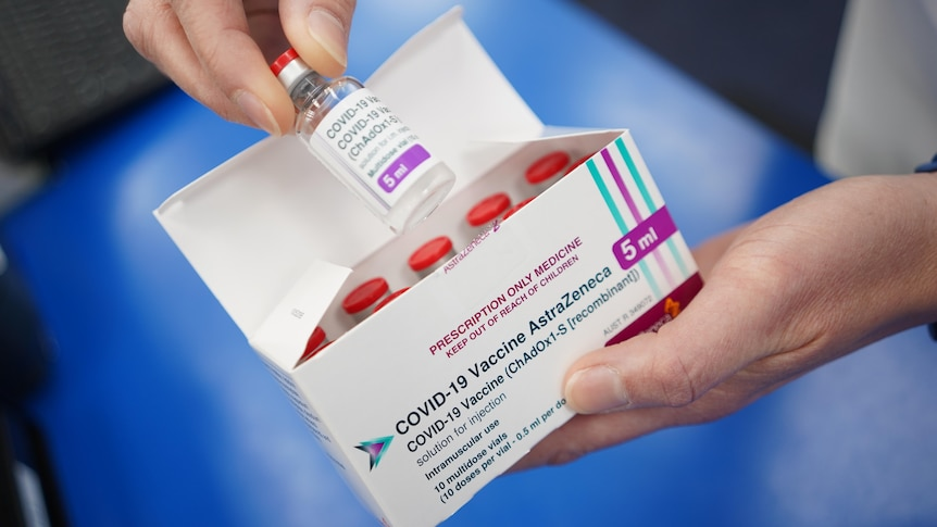 A vial of vaccine being pulled out of a box.