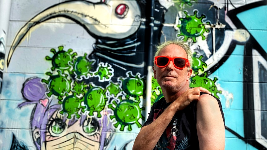 A man rolls up his sleeve with a colourful artwork wall.
