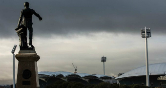 A statue of a man pointing his finger ahead overlooks an arena as skies of grey take over Adelaide.