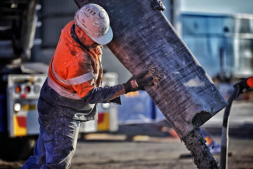A worker pours concrete at a building construction site in Brisbane.