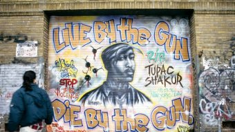 Mural of Tupac on garage door with words 'Live by the gun, die by the gun'.
