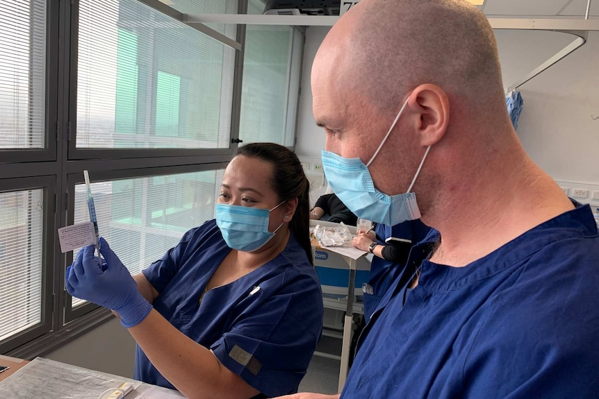 A woman and man in blue scrubs and masks prepare a syringe with a vaccine.