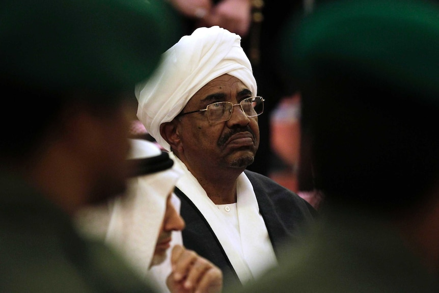 You see a close-up of Omar al-Bashir wearing white head robes as soft focus blurs two military guards on either side of his head