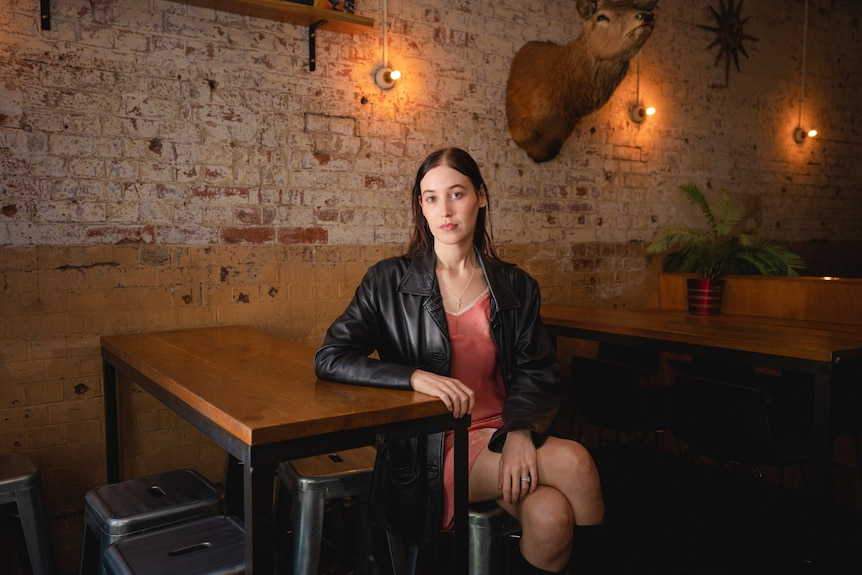 Harriette poses cross-legged at a table in an empty bar