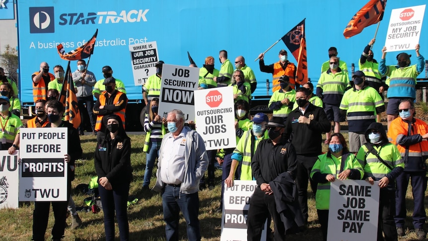 Workers waving flags and holding placards at a strike protest at StarTrack.