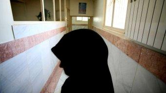 A female prison guard stands along a corridor in Tehran's Evin prison.