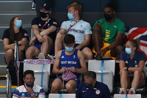 Tom Daley knits a dog jumper while sitting in the stands.