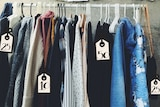 A rack of clothes hangs with price tags, they are old clothes being on-sold by their owners.