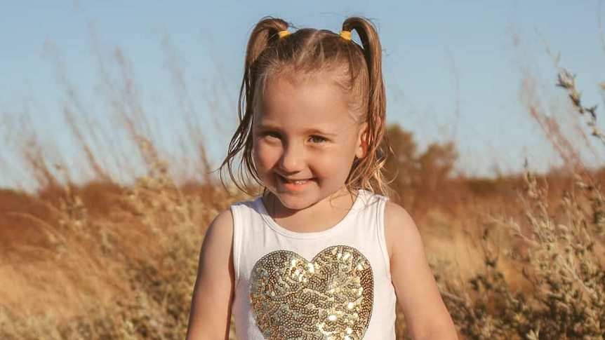A small child standing in an outback bush setting wearing a pretty dress.