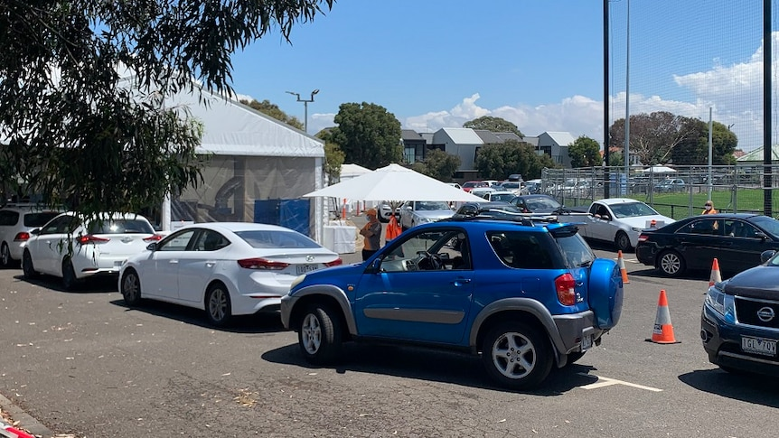 A queue of cars wait outside a tent for coronavirus testing.