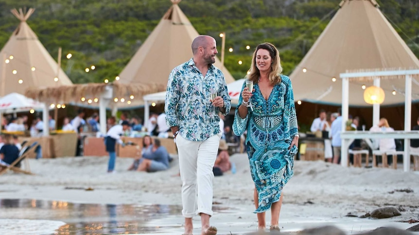 A man and woman are walking along the beach ion Margaret River, holding glasses of wine