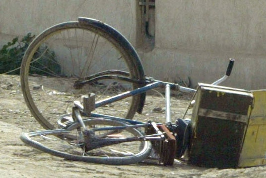 A blue bicycle lies on its side in street in Iraq.