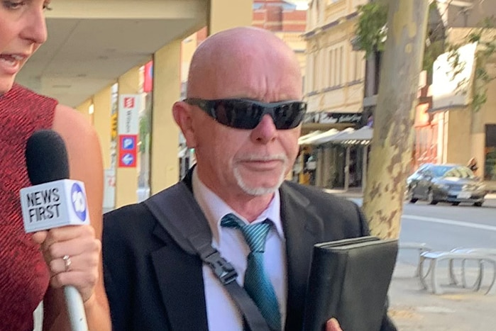 A man in sunglasses and a suit is questioned by a reporter with a microphone while walking down the street.