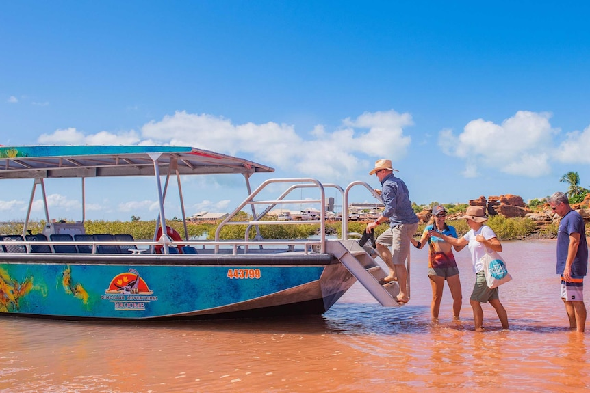 Tourists board a boat in water under a blue sky.