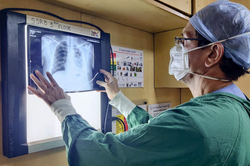 A man wearing a mask and a cap and dressed in scrubs stares at an x-ray of lungs.