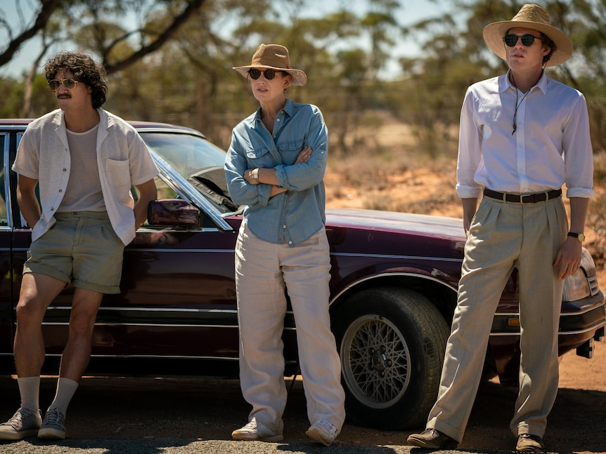 Three people stand alongside a car in hats and sunglasses, looking away into the distance