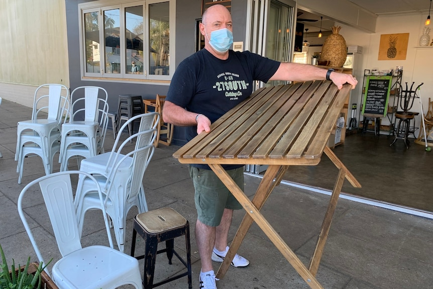 A man wearing a mask carries a wooden table at a cafe as he prepares to close