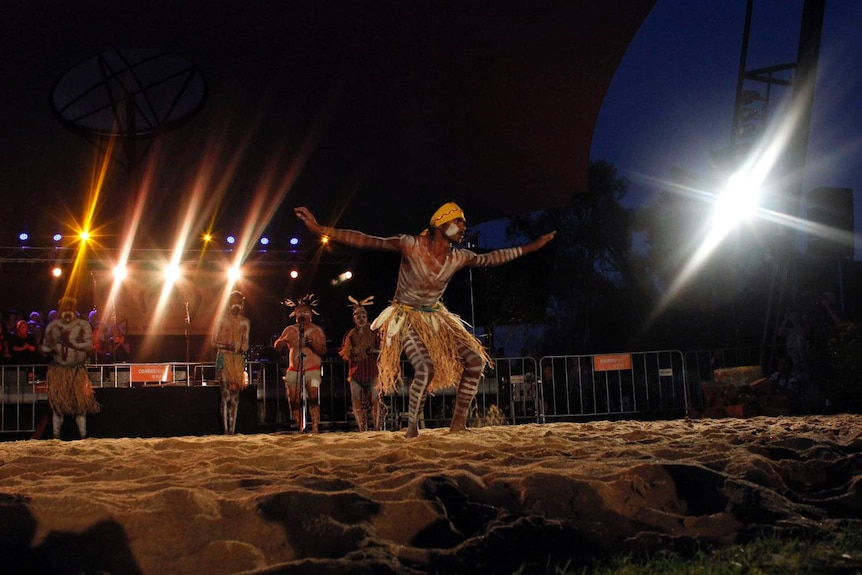 An Aboriginal man dancers in a grass skirt with marking in white paint on his body.