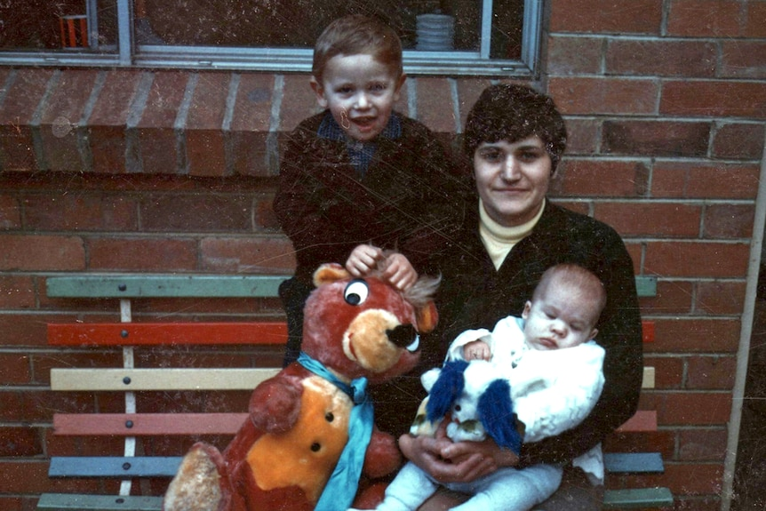 Maria James sits holding her youngest son Adam, beside her sits her oldest son Mark and a large stuffed animal