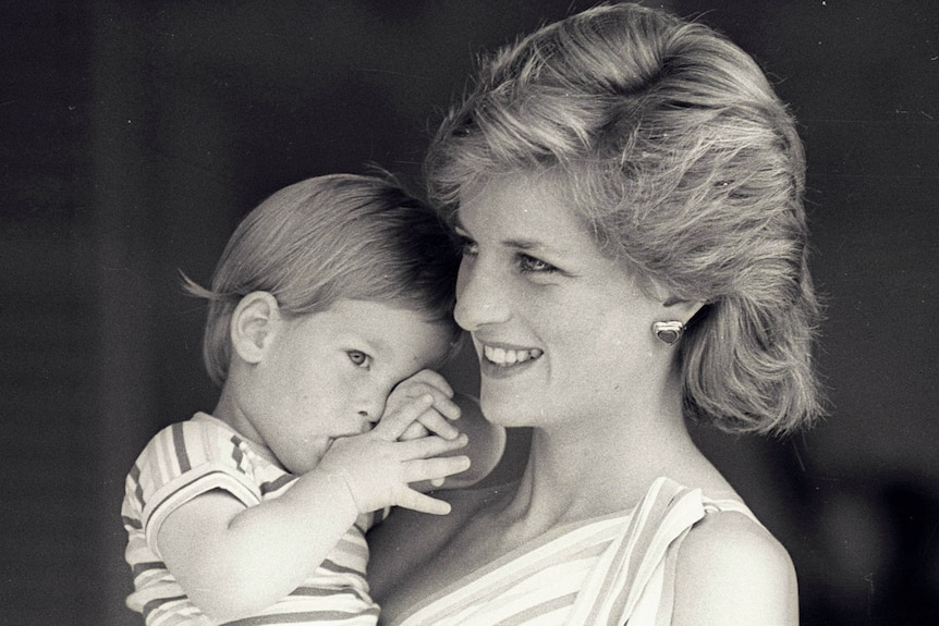 Princess Diana is holding a young Prince Harry.