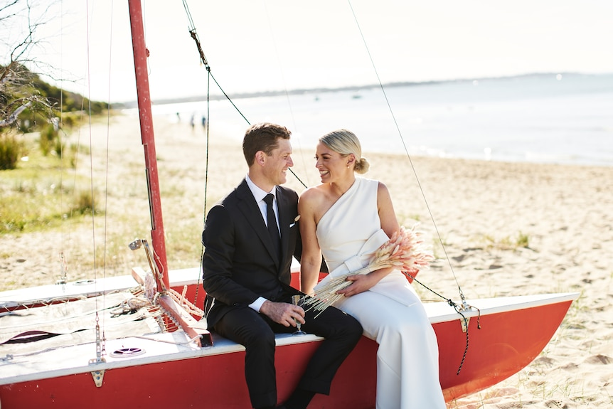 Chloe and James Devery on their wedding day, sitting on a beached yacht.