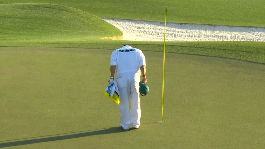A man wearing all white bows next to a flag on a golf green