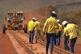 A crew in blue pants and yellow shirts work on a rail line with vehicle in background in the Pilbara