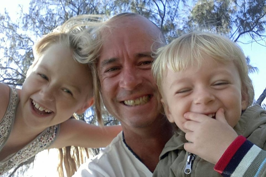 A man and two young children smile and laugh in a selfie with sky and trees in the background.