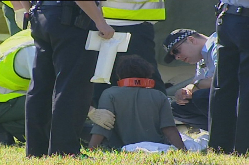 An Aboriginal boy sits on the ground after the fatal crash at Wilson, tended to by ambulance officers and police