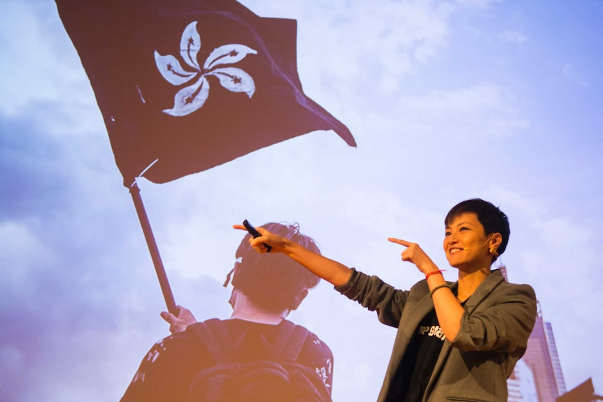 Denise Ho speaks in front of an image of a person waving a Hong Kong flag