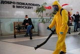A cleaner in full body protective gear uses equipment to disinfect an open public area at a train station in Moscow.