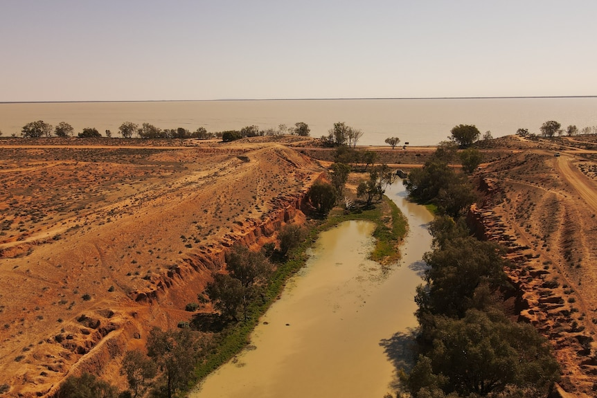 A narrow, muddy river flowing through dry, red earth