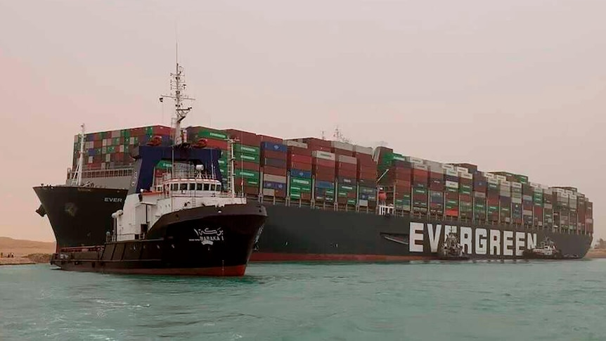 A boat navigates in front of a massive cargo ship, named the Ever Green,