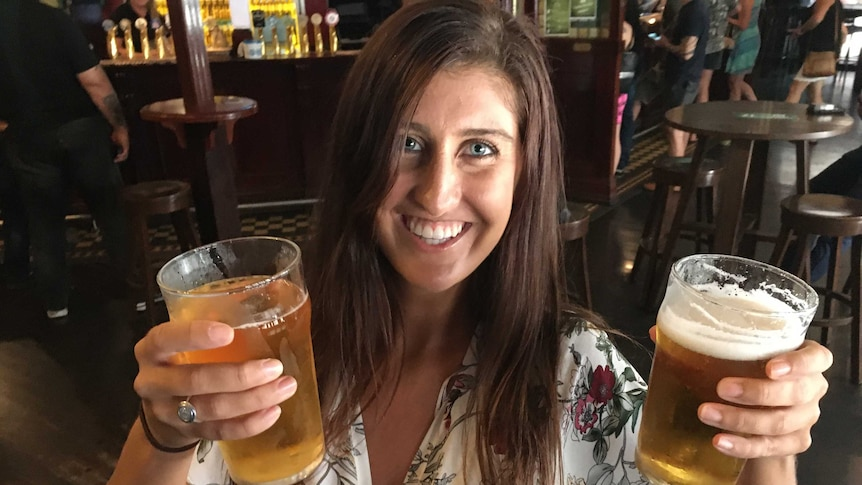 Charlotte Dubois holds two large drinks and smiles at the camera.